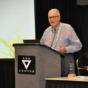 Male-presenting Elwood Richard standing behind a podium speaking