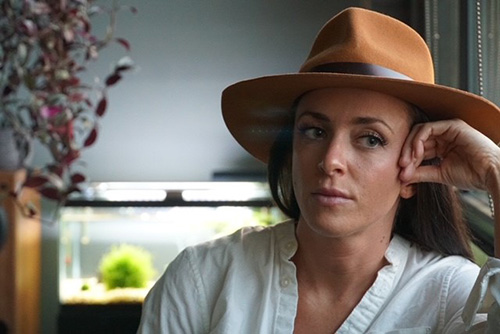 fawn dorr wearing a wide brim fedora looking pensively to the side