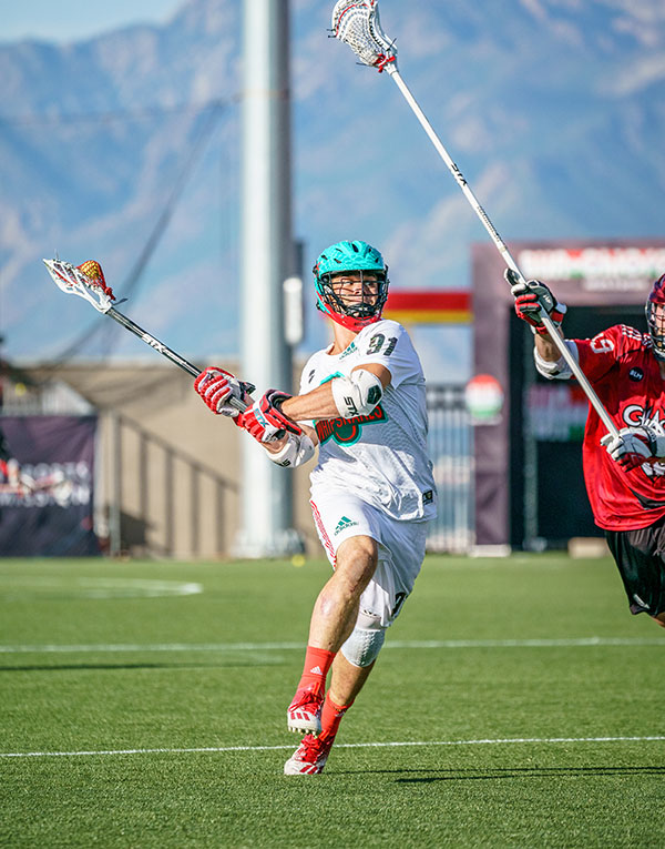 Joe Nardella playing lacrosse with a defender close by
