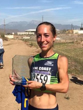 natalie larson ultra marathon runner holding trophy at end of race