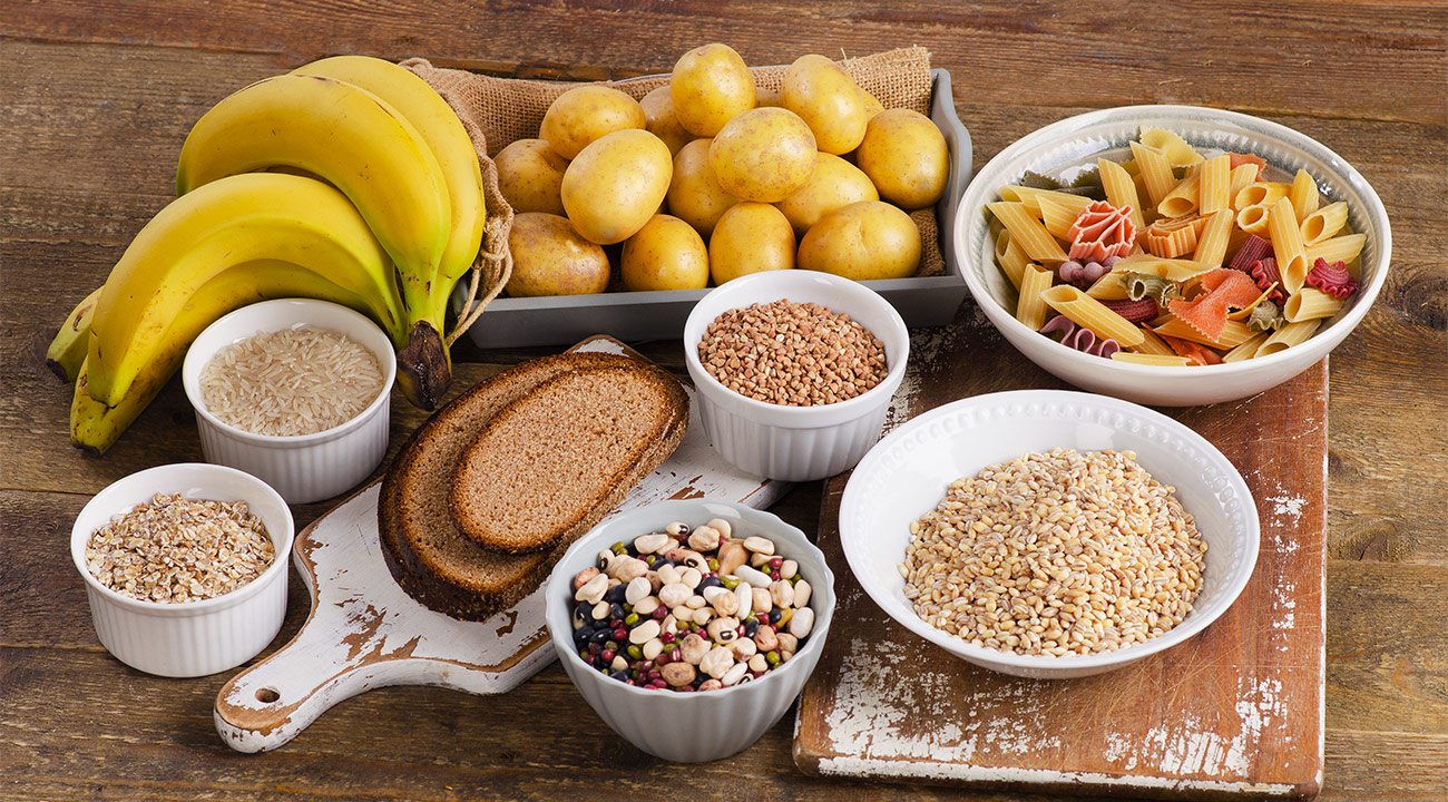 Several dishes, including bread, grains, potatoes, bananas, and pasta, are in white ceramic bowls placed on a rustic wooden table.