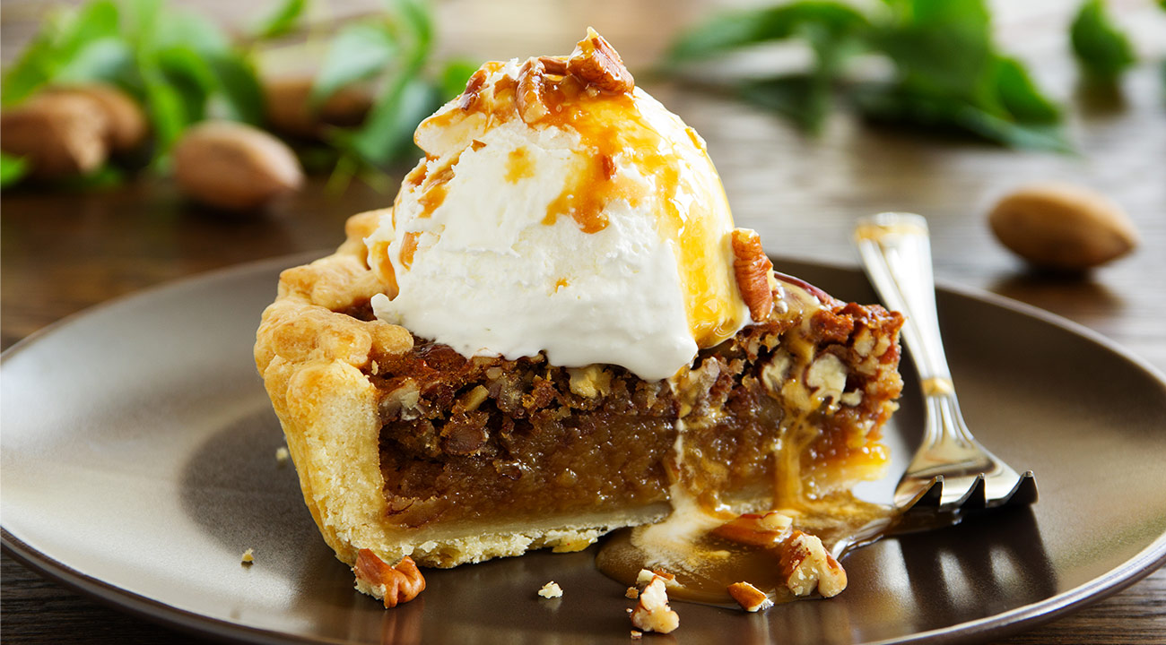 A brown plate holds a slice of holiday pie, topped with pecans, ice cream, and syrup.
