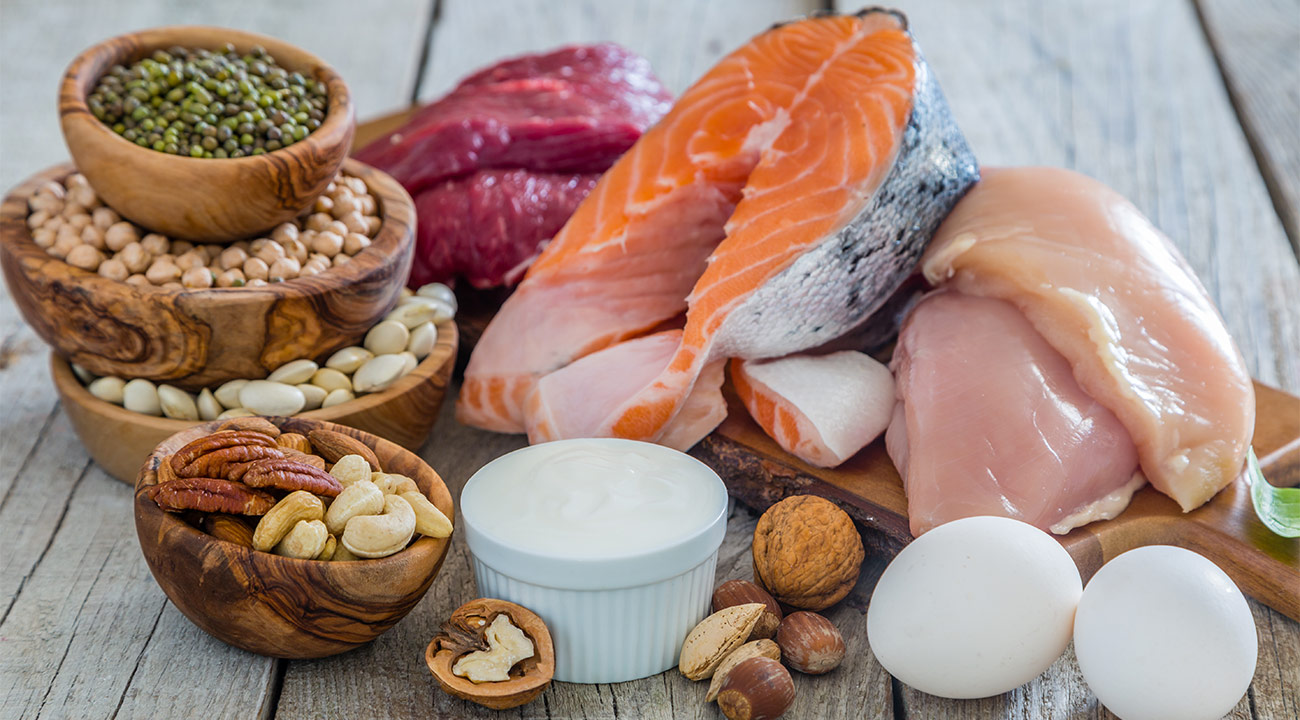 Several protein products, such as fish, eggs, chicken, beef, and different kinds of nuts are placed on a wooden table.